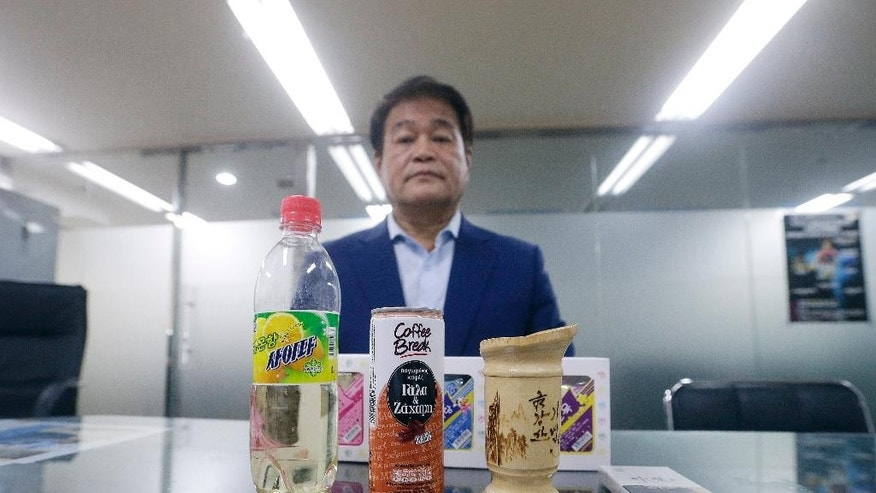 South Korean Lee In-gyeong, 62, who recently returned from North Korea after meeting with his uncle, North Korean Ri Hung Jong, 88, during the Separated Family Reunion Meeting, poses in his office in Seoul, South Korea, Friday, Oct. 23, 2015, with gifts of drinks, cigarettes and cookies that he received from his uncle. During an interview with the Associated Press, Lee recalled the heart-felt memories he will have of what is likely to be his last meeting with his uncle. (AP Photo/Ahn Young-joon)