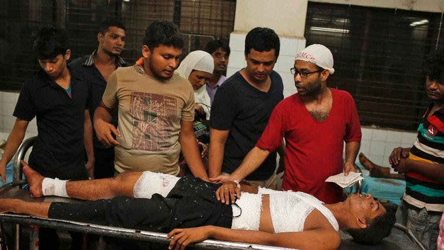 A Bangladeshi doctor, second right, attends to Ashikur Rahman, 22, injured in a bomb attack in Dhaka, Bangladesh, Saturday, Oct. 24, 2015. Unidentified attackers threw home-made bombs early Saturday at thousands of Shiite Muslims gathered for a traditional procession to a shrine in Bangladesh's capital. (AP Photo/A.M. Ahad)