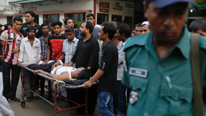 Ashikur Rahman, 22, who sustained injuries after an explosion, is carried on a stretcher outside a hospital in Dhaka, Bangladesh, Saturday, Oct. 24, 2015. Unidentified attackers threw home-made bombs early Saturday at thousands of Shiite Muslims gathered for a traditional procession to a shrine in Bangladesh's capital. (AP Photo/A.M. Ahad)