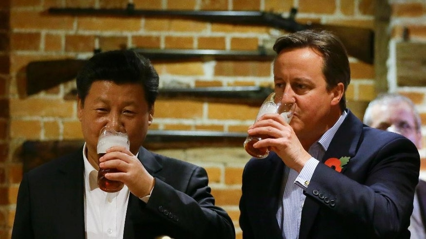 Britain's Prime Minister David Cameron, right, drinks beer with Chinese President Xi Jinping, at a pub in Princess Risborough, near Chequers, England, Thursday, Oct. 22, 2015.  The two leaders met for talks and dinner at the prime minister's official country residence Thursday, during a state visit hailed as a landmark by both China and Britain. (AP Photo/Kirsty Wigglesworth, pool)