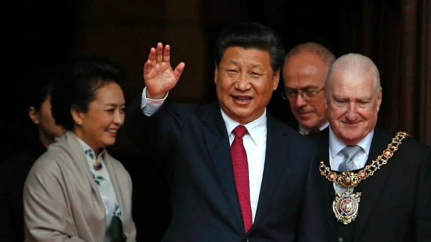 CORRECTS THE DAY TO FRIDAY China's President Xi Jinping, centre, waves as he leaves after lunch with Britain's Prime Minister David Cameron at Manchester Town Hall in Manchester, England, Friday,  Oct. 23, 2015 on the final day of his state visit. in the background is his wife Peng Liyuan. (Phil Noble/Pool Photo via AP)