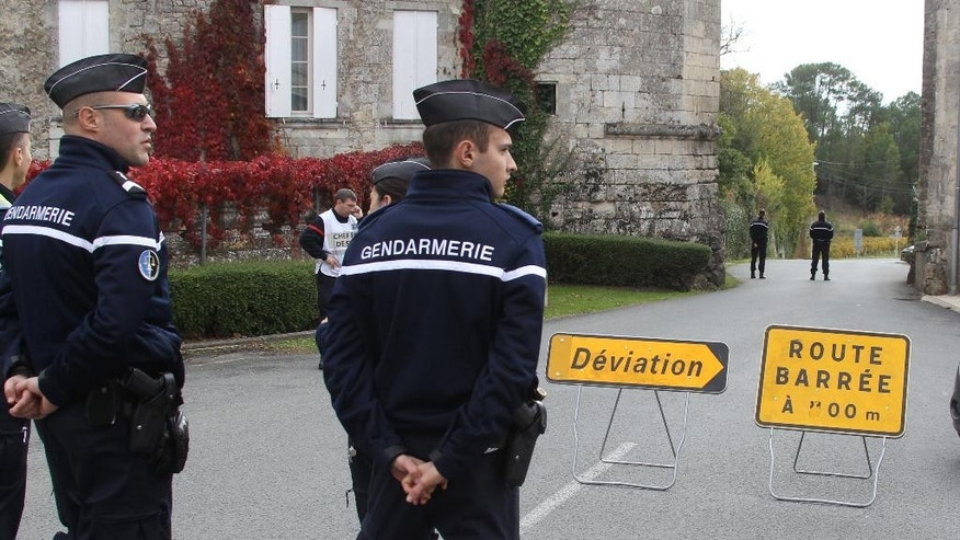 French gendarmes prevent media access to the site of a bus crash in Puisseguin, near Bordeaux, southwestern France, following a road accident in which at least 42 people were killed, Friday, Oct. 23, 2015. A truck and a bus transporting retirees on a day trip collided and caught fire Friday on a country road in wine country in southwest France, killing 42 people and gravely injuring at least four others, authorities said. (AP Photo/Bod Edme)