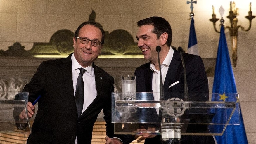 Greek Prime minister Alexis Tsipras, right,  and French President Francois Hollande, arrive for a press conference after their meeting in Athens, Friday, Oct. 23, 2015. Hollande called Thursday for talks relieving Greece's crushing debt load and spurring investment, measures that could help the country recover as it imposes harsh austerity measures demanded by international creditors.(AP Photo/Petros Giannakouris10