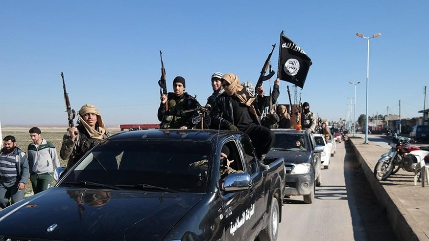 FILE - In this this file photo released on May 4, 2015, on a militant website, which has been verified and is consistent with other AP reporting, Islamic State militants pass by a convoy in Tel Abyad, northeast Syria. The Islamic State rakes in up to $50 million a month from selling crude from oilfields under its control in Iraq and Syria, part of a well-run oil industry that U.S. diplomacy and airstrikes have so far failed to shut down, according to Iraqi intelligence and U.S. officials.(Militant website via AP, File)