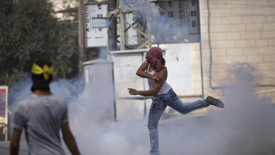 A Palestinian protester throws back a tear gas canister that was fired by Israeli troops during clashes, in the West Bank town of al-Ram, north of Jerusalem, Thursday, Oct. 22, 2015.  Ten Israelis have been killed over the last month, mainly in stabbing attacks. On the Palestinian side, 48 people have been killed. The violence erupted a month ago, fueled by rumors that Israel was plotting to take over a sensitive Jerusalem holy site revered by both Jews and Muslims. (AP Photo/Majdi Mohammed)
