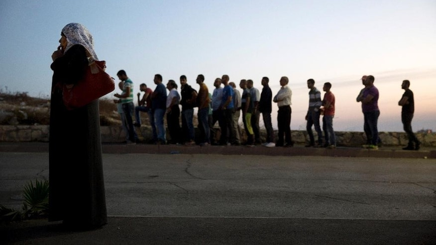 Palestinians wait in line to cross an Israeli police checkpoint as they exit the Arab neighborhood of Issawiyeh in Jerusalem, Thursday, Oct. 22, 2015. Israel has beefed up security across the country, sending hundreds of soldiers to back up thousands of police officers. Police have erected concrete barriers and checkpoints at the entrance to Arab areas of east Jerusalem, where many of the attackers are from. (AP Photo/Oded Balilty)