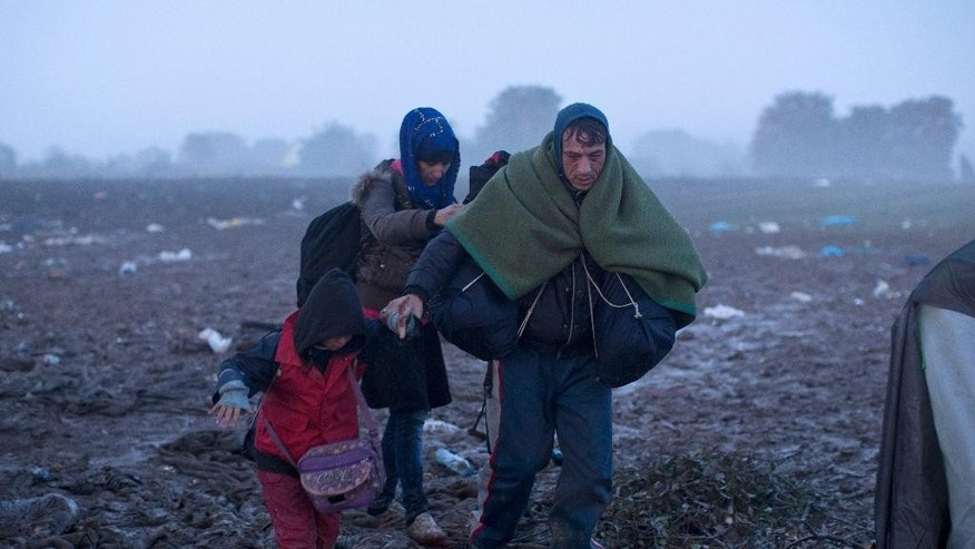 A family treks through a muddy field towards the Serbia's border with Croatia, in Berkasovo, Serbia, Friday, Oct. 23, 2015. Most migrants fleeing war and poverty in the Middle East, Asia and Africa wish to go to Germany or other wealthier countries of Western Europe. (AP Photo/Marko Drobnjakovic)