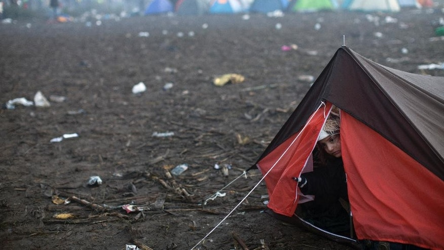 A girl peers out of a tent close to Serbia's border with Croatia, in Berkasovo, Serbia, Friday, Oct. 23, 2015. Most migrants fleeing war and poverty in the Middle East, Asia and Africa wish to go to Germany or other wealthier countries of Western Europe. (AP Photo/Marko Drobnjakovic)