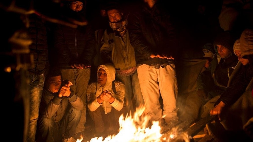 People try to stay warm by a fire close to Serbia's border with Croatia, in Berkasovo, Serbia, Friday, Oct. 23, 2015. Most migrants fleeing war and poverty in the Middle East, Asia and Africa wish to go to Germany or other wealthier countries of Western Europe. (AP Photo/Marko Drobnjakovic)