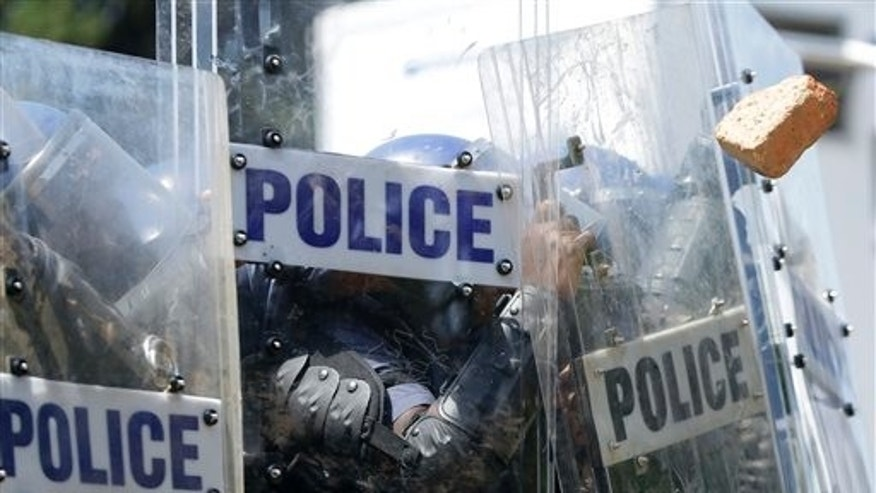 Riot police officers shield off stones thrown by students during their protest against university tuition hikes outside the union building in Pretoria, South Africa, Friday. (AP Photo/Themba Hadebe)