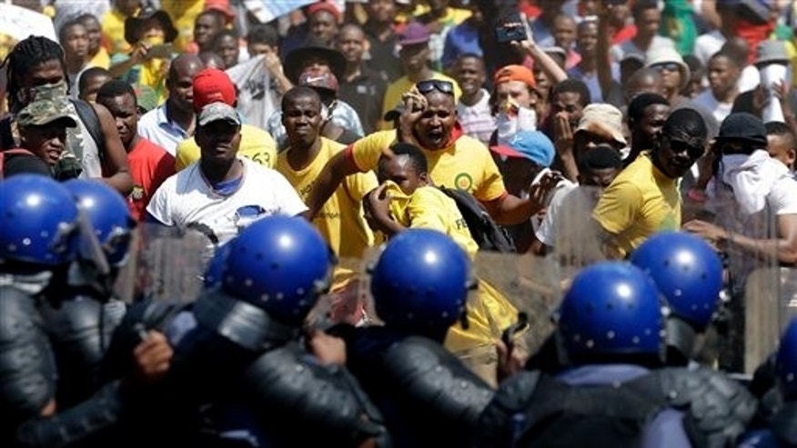 Students throw stones against riot police officers during their protest against university tuition hikes outside the union building in Pretoria, South Africa, Friday. (AP Photo/Themba Hadebe)