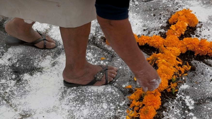 "A woman makes a couple of crosses out of flowers at the exact place where a mob beat, killed and burned two pollsters who were conducting a survey, in front of the Municipal Palace in Ajalpan, Puebla, Mexico, Wednesday, October 21, 2015. Gabriela Vazquez, president of a parents' committee who is also an Ajalpan police officer said: ""The town will live with remorse knowing what it has done."" (AP Photo/Marco Ugarte)"