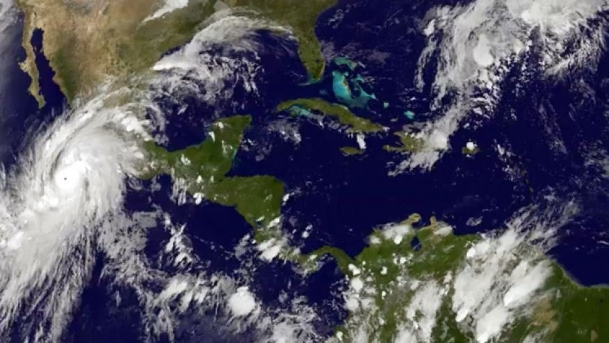 This satellite image taken at 8:45 p.m. EDT on Thursday, Oct. 22, 2015, and released by the National Oceanic and Atmospheric Administration shows Hurricane Patricia, left, moving over Mexico's central Pacific Coast. The powerful Category 4 storm bore down on Mexico's central Pacific Coast on Thursday night, for what forecasters said could be a devastating blow, as officials declared a state of emergency and handed out sandbags in preparation for flooding. (NOAA via AP)