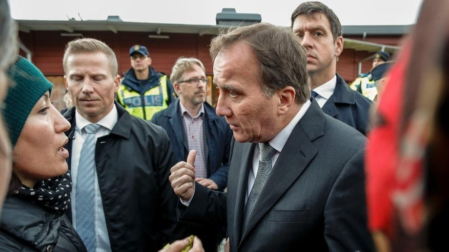 Prime Minister Stefan Lofven, right, talks to local people near the school Thursday afternoon where a masked man wielding what looked like a sword stabbed four people Thursday Oct. 22, 2015, in Trollhattan, Southern Sweden. A knife-wielding masked man stabbed four people Thursday at a school in southern Sweden, killing one teacher and a student before being shot by police, authorities said. (Adam Ihse/TT via AP) SWEDEN OUT