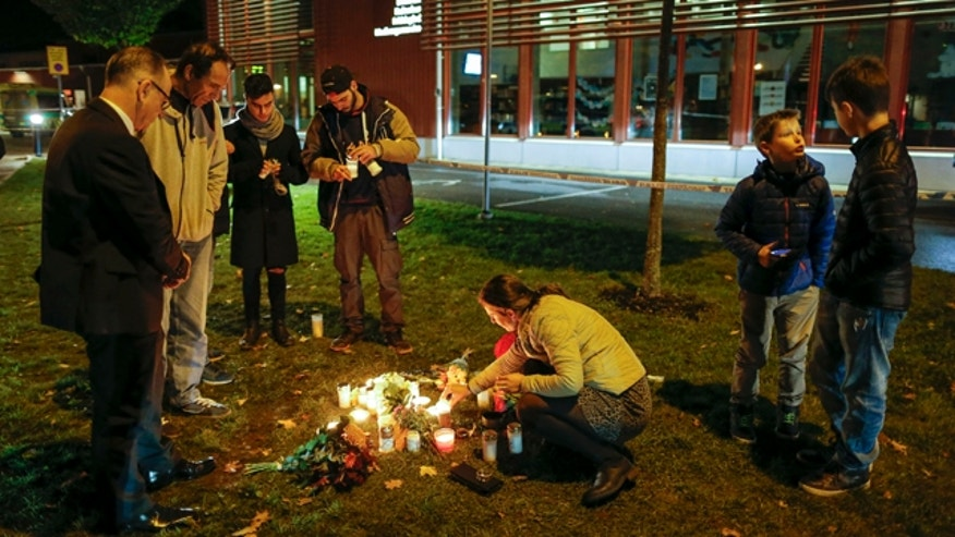 Oct. 22, 2015: People light candles and lay flower tributes outside the school where a masked man stabbed four people in Trollhattan,  Sweden. The man killed one teacher and a student before being shot by police, authorities said. (Adam Ihse/TT via AP)
