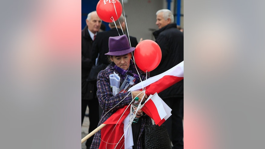A supporter of the conservative opposition Law and Justice party that is considered a favorite in Sunday general elections, with national flags and balloons leaves  after a party convention that wrapped up months of campaigning in Warsaw, Poland, on Thursday, Oct.22, 2015. ( AP Photo/Czarek Sokolowski)
