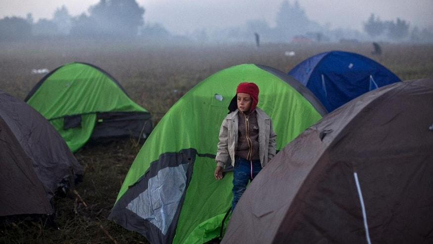 A boy stands next to tents in which families of migrants and refugees spent the night, close to Serbia's border with Croatia, in Berkasovo, Serbia, Friday, Oct. 23, 2015. Most migrants fleeing war and poverty in the Middle East, Asia and Africa wish to go to Germany or other wealthier countries of Western Europe. (AP Photo/Marko Drobnjakovic)
