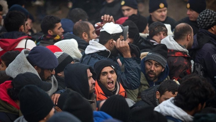 A man shouts while standing in a crowd of people waiting to clear a police line close to Serbia's border with Croatia, in Berkasovo, Serbia, Friday, Oct. 23, 2015. Most migrants fleeing war and poverty in the Middle East, Asia and Africa wish to go to Germany or other wealthier countries of Western Europe. (AP Photo/Marko Drobnjakovic)
