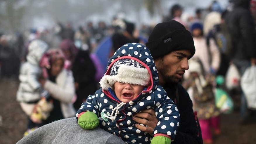 A man carries a crying child as he and his family members try to cross from Serbia into Croatia, in Berkasovo, Serbia, Friday, Oct. 23, 2015. Most migrants fleeing war and poverty in the Middle East, Asia and Africa wish to go to Germany or other wealthier countries of Western Europe. (AP Photo/Marko Drobnjakovic)