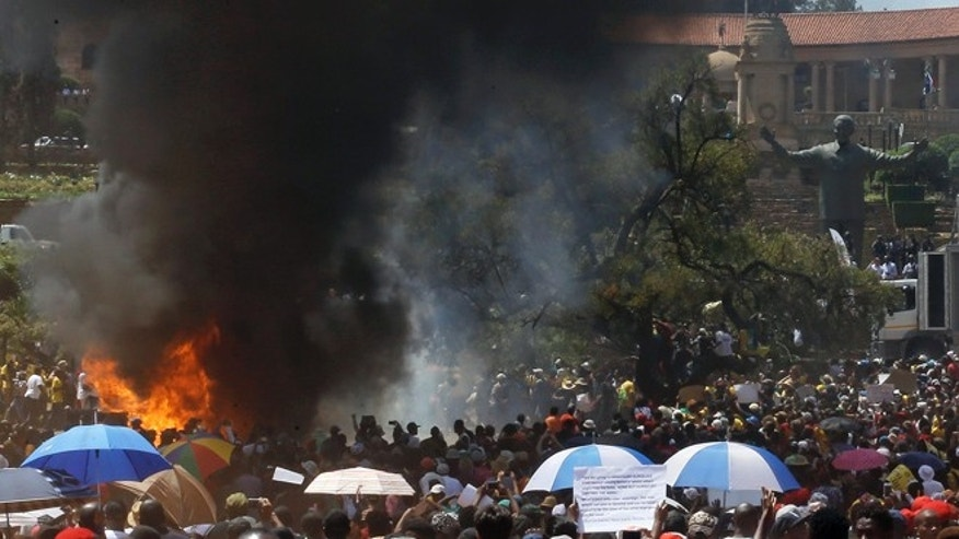 Oct. 23, 2015: Students burn portable toilets during their protest against university tuition hikes outside the union building in Pretoria, South Africa.