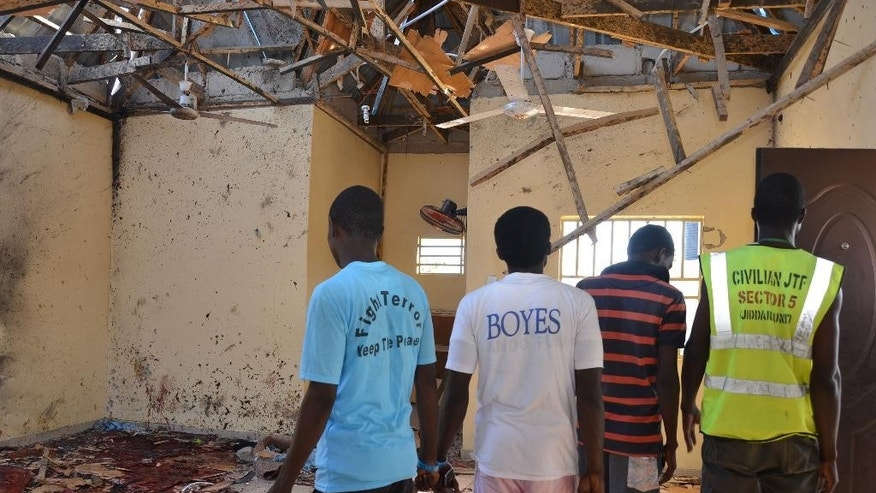People inspect a damaged mosque following an explosion in Maiduguri, Nigeria, Friday, Oct. 23, 2015.  A self-defense fighter says twin bomb blasts have killed at least 18 at a northeast Nigerian mosque crowded with people observing pre-dawn prayers. (AP Photo/Jossy Ola)