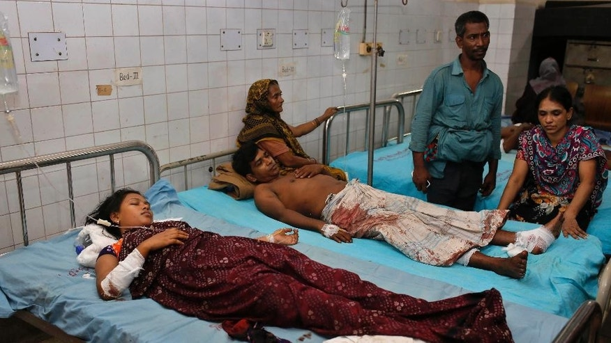 Halima Akhter, 20, left, and her husband Munir Hossain, 35, who sustained injuries after an explosion, receive treatment at a hospital in Dhaka, Bangladesh, Saturday, Oct. 24, 2015. Unidentified attackers threw home-made bombs early Saturday at thousands of Shiite Muslims gathered for a traditional procession to a shrine in Bangladesh's capital. (AP Photo/A.M. Ahad)