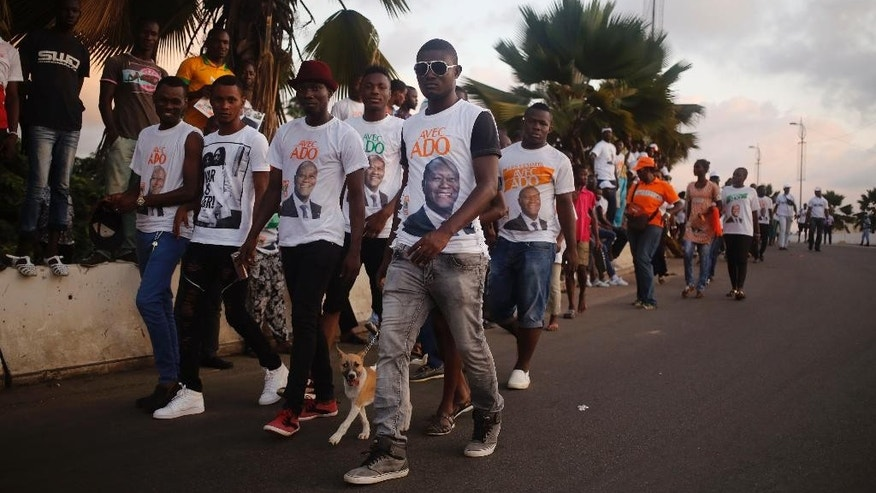 Supporters of  Ivory Coast incumbent President Alassane Ouattara walk, during an election rally  in Abidjan, Ivory Coast, Friday, Oct. 23, 2015.  Ivory Coast's president is widely expected to win a second term as the West African nation votes Sunday, five years after a disputed poll that spilled over into the worst violence the country has experienced since independence.  (AP Photo/Schalk van Zuydam)