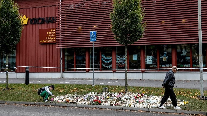 A boy adds a candle to a collection of flowers and candles placed outside the Kronan school in Trollhattan, Sweden, the scene of Thursday's attack, in Tollhattan, Saturday, Oct. 24, 2015.  A masked man with a sword and knife attacked students and teachers, killing two and seriously wounding two others. (Adam Ihse/TT via AP)