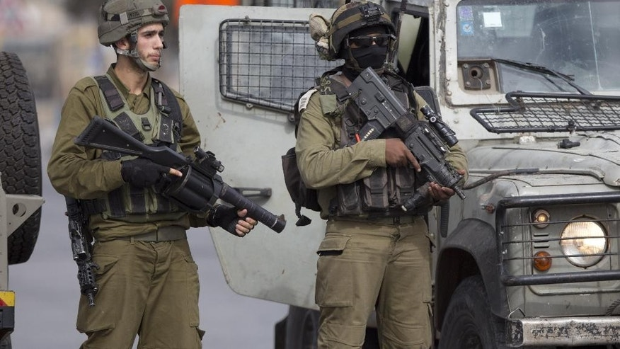 Israeli security forces stand guard as they prevent Palestinians from approaching the area where Palestinian Ahmed Ikmel,16, was killed Saturday after he allegedly attempted to stab an Israeli security guard at the Jalama checkpoint near Jenin, West Bank, Saturday, Oct. 24, 2015. The military said the incident took place at a crossing between Israel and the West Bank. (AP Photo/Majdi Mohammed)