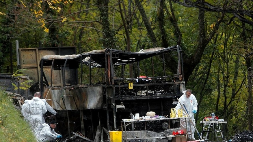 Forensic experts inspect the charred wreckage of a truck and a bus involved in a fatal crash which killed over 40 people near the village of Puisseguin, southwestern France, Saturday, Oct. 24, 2015. A truck and a bus transporting retirees on a day trip collided and caught fire Friday on a country road in wine country in southwest France, killing 42 people and gravely injuring at least four others, authorities said. (AP Photo/Thibault Camus)