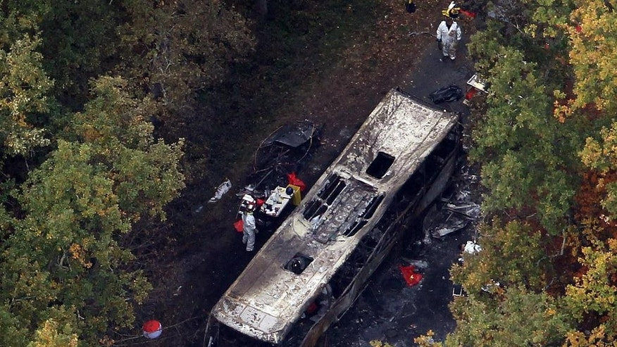 In this aerial photo, French forensic experts work after a truck and a bus transporting retirees on a day trip collided and caught fire Friday, killing 42 people and badly injuring four others, near the village of Puisseguin, about 50 kilometers (30 miles) east of Bordeaux, France, Saturday Oct. 24, 2015. Eight people, including the driver, escaped from the bus, in the nation's deadliest road accident in more than 30 years. (AP Photo/Bob Edme)