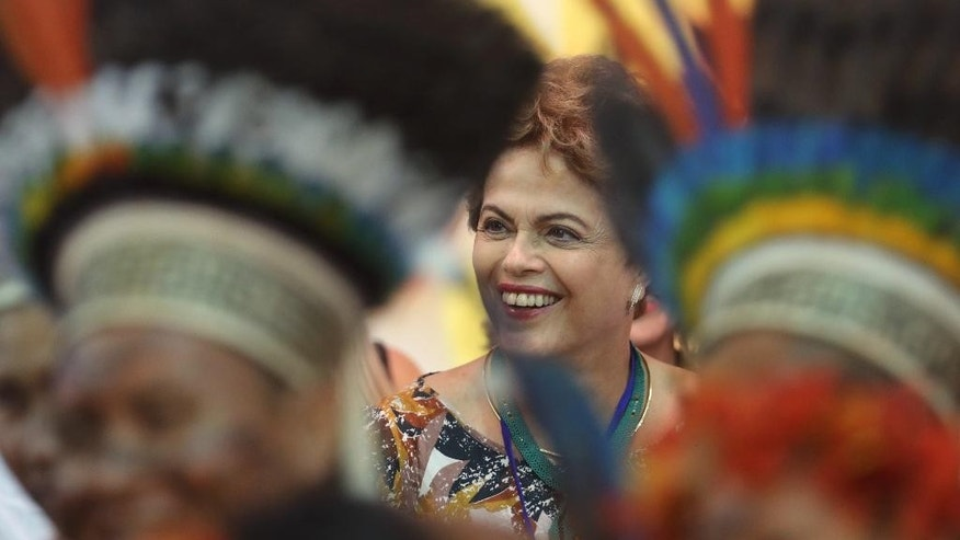 CORRECTS SPELLING OF ROUSSEFF - Brazil's President Dilma Rousseff watch indigenous dances before the opening ceremony of the World Indigenous Games in Palmas, Brazil, Friday, Oct. 23, 2015. Billed as the indigenous Olympics, the games are expected to attract nearly 2,000 athletes from dozens of Brazilian ethnicities, as well as from such far-flung nations as Ethiopia and New Zealand. (AP Photo/Eraldo Peres)