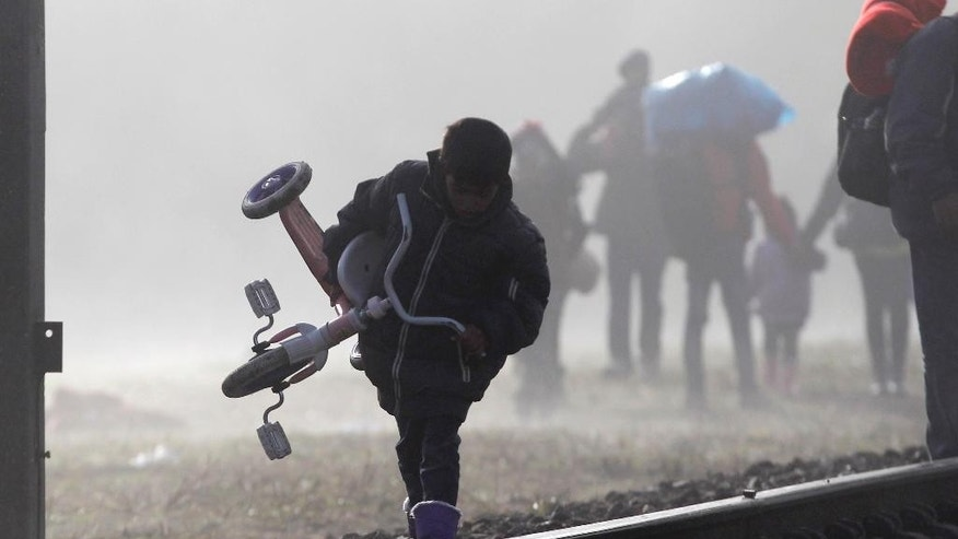 A boy carries a tricycle on a train track on a misty morning in Spielfeld, Austria, Saturday, Oct. 24, 2015. Thousands of people are trying to reach central and northern Europe via the Balkans but often have to wait for days in mud and rain at the Serbian, Croatian and Slovenian borders. (AP Photo/Petr David Josek)
