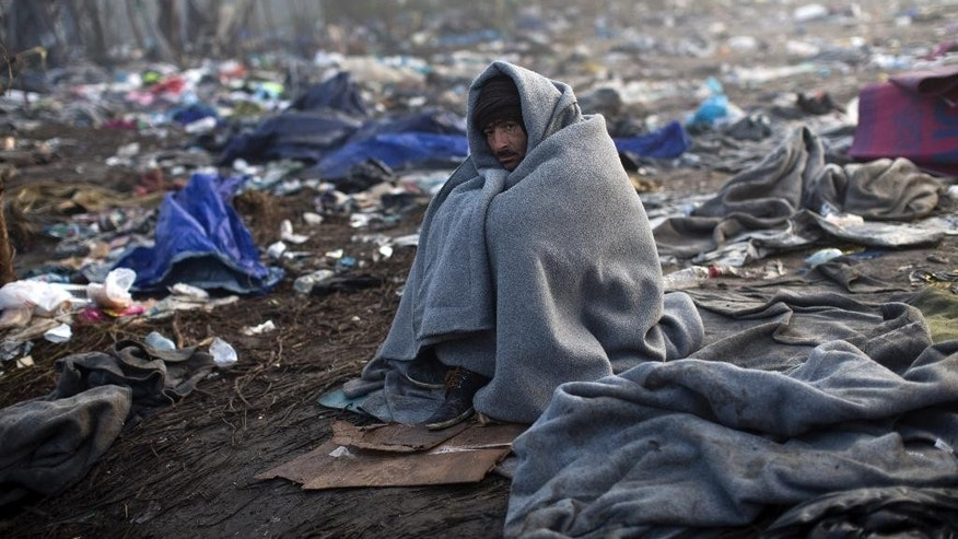 A man stays warm by wrapping himself in a blanket as he waits to cross Serbia's border with Croatia in Berkasovo, Serbia, Saturday, Oct. 24, 2015. Thousands of migrants and refugees are still crossing from Serbia into Croatia and continuing their journey towards Western Europe. (AP Photo/Marko Drobnjakovic)