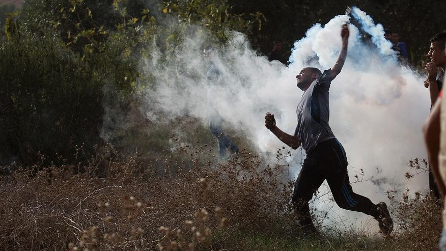 A Palestinian protester throws back a tear gas canister during clashes with Israeli soldiers by the Israeli border with Gaza east of Bureij refugee camp, central Gaza Strip, Friday, Oct. 23, 2015. Elsewhere, Muslim prayers at Jerusalem's holiest site, which has been the epicenter of weeks of unrest, ended peacefully on Friday as the first time in weeks of escalating violence, Israel allowed Muslims of all ages to enter the site to perform prayers in an apparent bid to ease tensions. (AP Photo/Adel Hana)