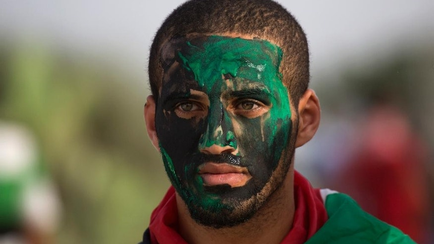 A Palestinain protester paints his face during clashes with Israeli solders during clashes at the Israeli border with Gaza east of Bureij refugee camp, central Gaza Strip, Friday, Oct. 23, 2015. Elsewhere, Muslim prayers at Jerusalem's holiest site, which has been the epicenter of weeks of unrest, ended peacefully on Friday as the first time in weeks of escalating violence, Israel allowed Muslims of all ages to enter the site to perform prayers in an apparent bid to ease tensions. (AP Photo/Adel Hana)