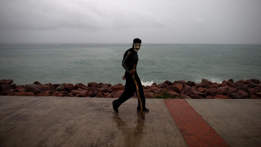 A young man wears a skull mask, which he said was to protect himself from the rain, as he walks along the waterfront while rain strengthens with the approach of Hurricane Patricia in Puerto Vallarta, Mexico, Friday, Oct. 23, 2015. Hurricane Patricia barreled toward southwestern Mexico Friday as a monster Category 5 storm, the strongest ever in the Western Hemisphere. (AP Photo/Rebecca Blackwell)