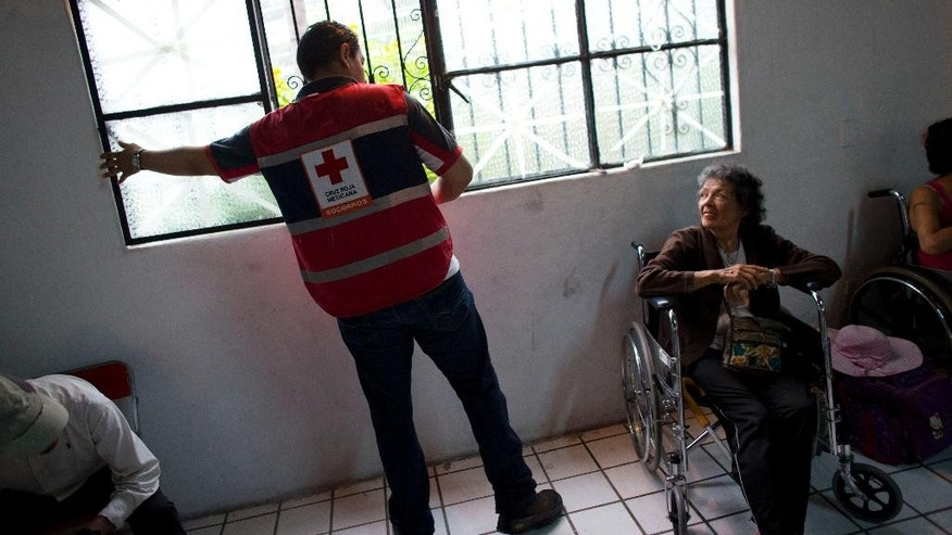A Red Cross worker opens a window to air out the room where residents and tourists take refuge before the arrival of Hurricane Patricia at a small shelter in Puerto Vallarta, Mexico, Friday, Oct. 23, 2015. Hurricane Patricia barreled toward southwestern Mexico Friday as a monster Category 5 storm, the strongest ever in the Western Hemisphere. (AP Photo/Rebecca Blackwell)