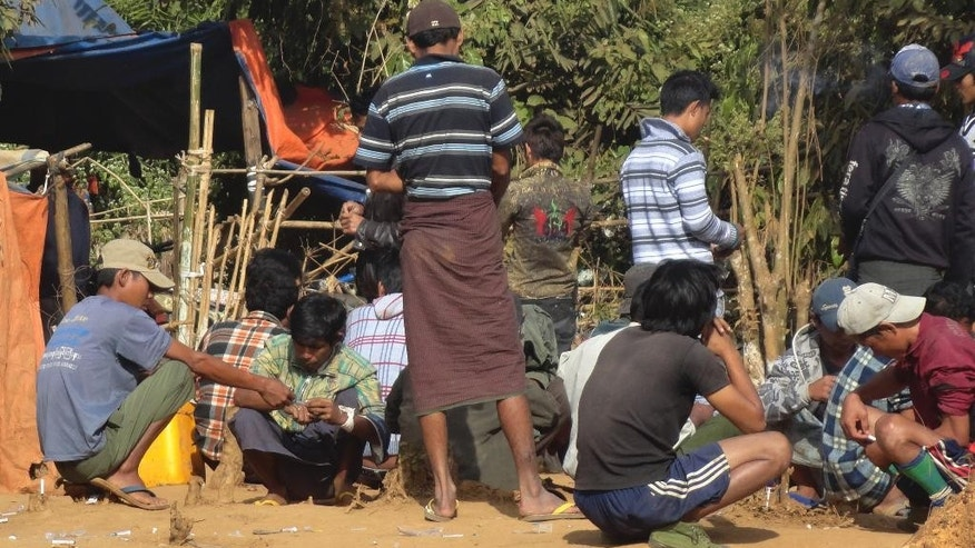 In this October 2014, photo, men use syringes as they inject drugs near the jade mines surrounding Hpakant, in Kachin state, some 720 kilometers (600 miles) north of Yangon, Myanmar. With drug use on the rise, residents of this town in northern Myanmar's opium country became their own drug investigators out of frustration with authorities' inability to keep heroin and methamphetamine addiction from consuming their villages. (AP Photo)