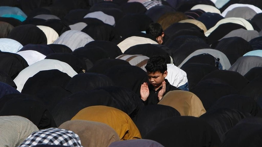 Pakistani Shiite Muslims offer prayers during a Muharram rally ahead of Ashoura day, in Karachi, Pakistan, Friday, Oct. 23, 2015. Ashoura is a Shiite Muslim commemoration marking the death of Hussein, the Prophet Muhammad's grandson, at the Battle of Karbala in present-day Iraq. (AP Photo/Shakil Adil)