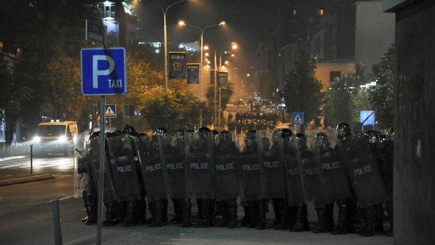 Kosovo police officers in riot gear stand in a formation to disperse supporters of opposition parties outside Kosovo's parliament, in Pristina, Kosovo, on Friday, Oct. 23, 2015. Kosovo's Parliament on Friday suspended its session for the second time in a day when opposition lawmakers protesting the government's agreements with Serbia and Montenegro threw tear gas canisters in the chamber.  (AP Photo/str)