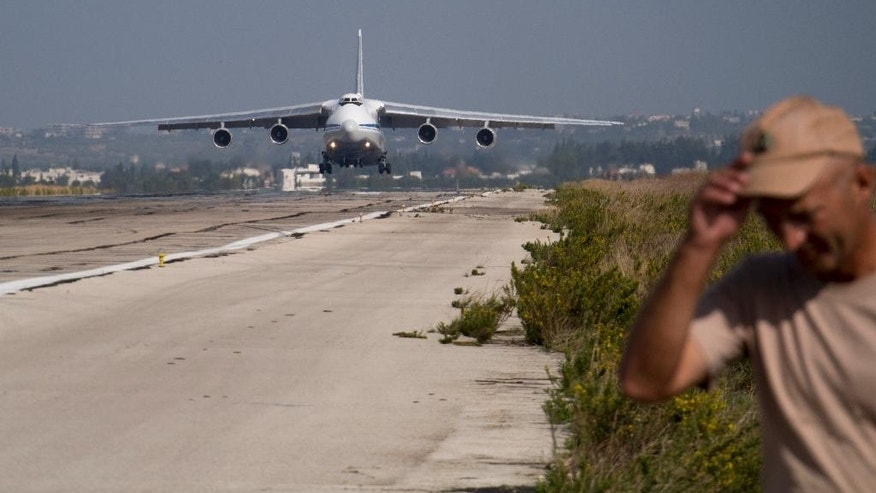 In this photo taken on Thursday, Oct.  22, 2015, A Russian transport plane lands at Hemeimeem airbase, Syria. Nearly a quarter of a century after the Soviet collapse, the air campaign in Syria has proven that the resurgent Russian military machine could again operate far away from the nation's borders. (AP Photo/Vladimir Isachenkov)