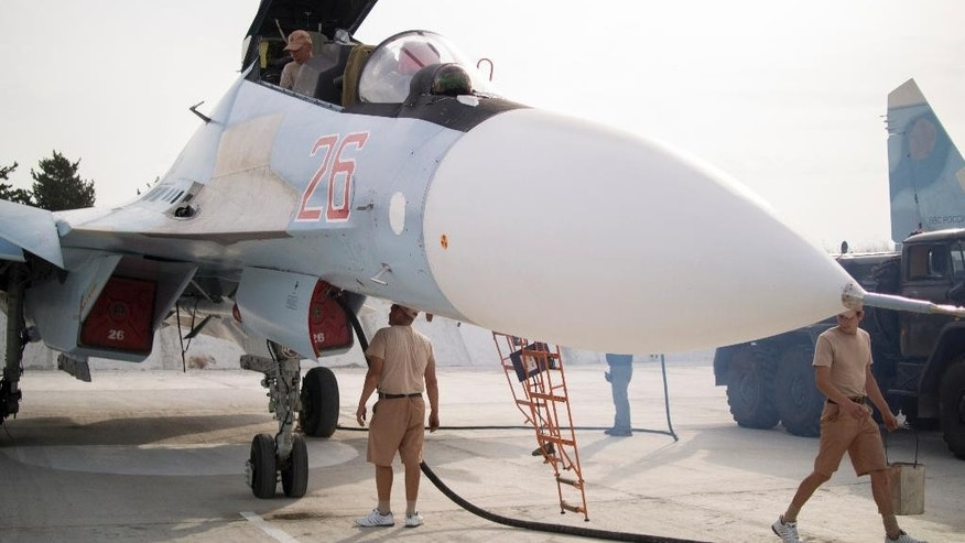 In this photo taken on Thursday, Oct.  22, 2015, Russian air force technicians service a Russian fighter jet at Hemeimeem airbase, Syria. Nearly a quarter of a century after the Soviet collapse, the air campaign in Syria has proven that the resurgent Russian military machine could again operate far away from the nation's borders. (AP Photo/Vladimir Isachenkov)