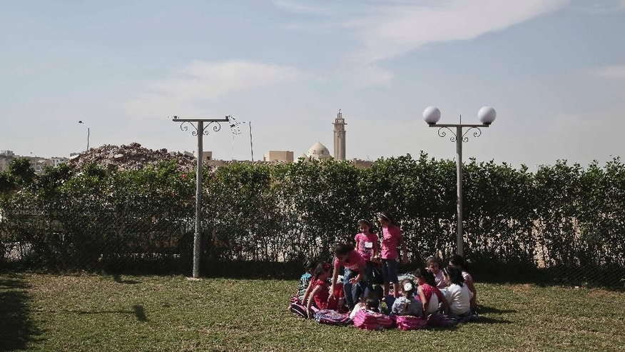 In this Monday, Oct. 12, 2015, photo, Syrian refugee girls play during their break time at the Civilization Builders Educational Center in the 6th of October suburb west of Cairo. The Civilization Builders Educational Center is one of several centers in 6th of October established to provide a better learning environment for the refugees. (AP Photo/Nariman El-Mofty)