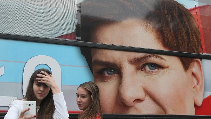 Supporters of the conservative opposition Law and Justice party that is considered a favorite in Sunday general elections take  a selfie in front of the campaign bus of Beata Szydlo, the  party's candidate for prime minister, after a party convention that wrapped up months of campaigning in Warsaw, Poland, on Thursday, Oct. 22, 2015.(AP Photo/Czarek Sokolowski)