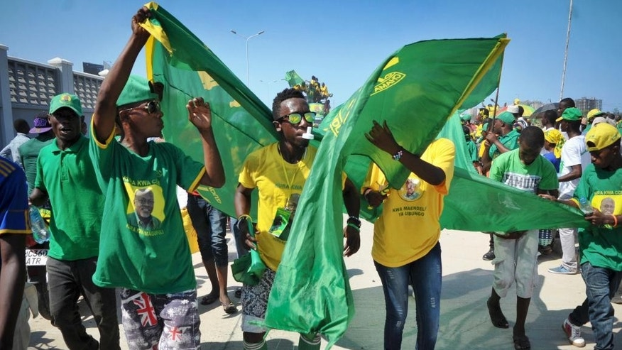Supporters wave flags, blow whistles, and wear t-shirts showing the face of presidential candidate John Magufuli of the ruling Chama Cha Mapinduzi (CCM) party, at an election rally in Dar es Salaam, Tanzania, Friday, Oct. 23, 2015. Tanzanians vote Sunday in landmark elections that could end the dominance of the ruling party, which has held power for decades but faces a united opposition buoyed by growing discontent over official corruption. (AP Photo/Khalfan Said)