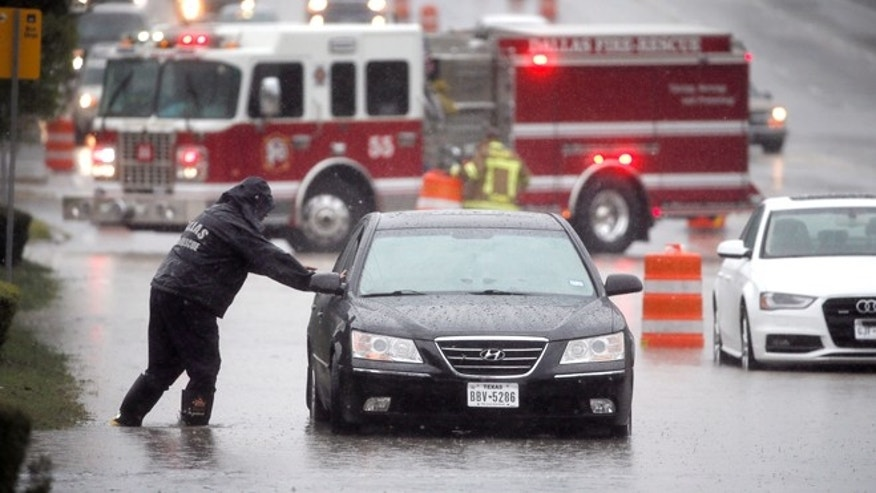 A Dalls Fire Rescue responder makes his way over to a stalled vehicle to check on the driver still inside on Friday, Oct. 23, 2015, in Dallas. The vehicle stalled after the road quickly flooded during a heavy rain fall. (AP Photo/Tony Gutierrez)