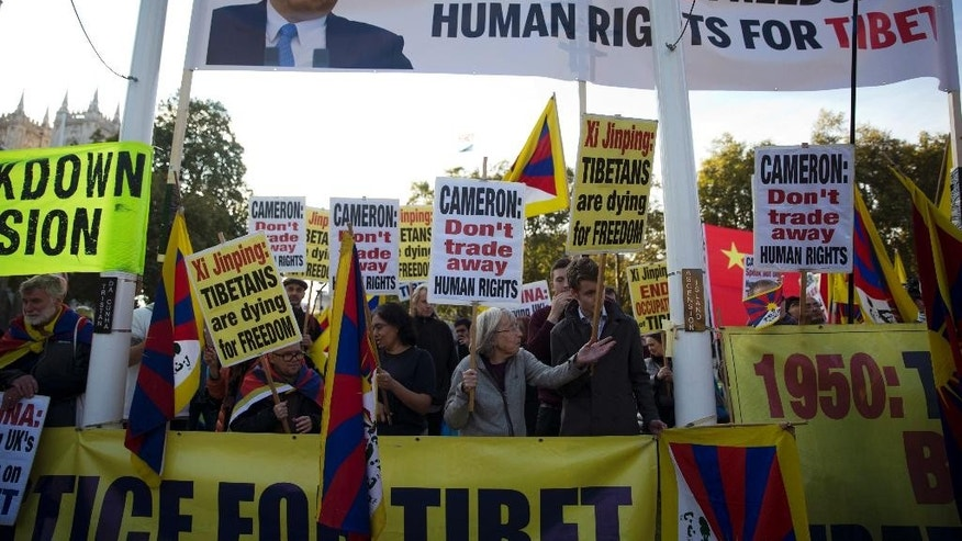 FILE - In this Oct. 20, 2015 file photo, human rights demonstrators stand beneath a protest banner bearing an image of Chinese President Xi Jinping on Parliament Square outside the Houses of Parliament, where he was giving a speech in London. Veteran Chinese pro-democracy campaigners have protested Britain's treatment of an activist detained during Chinese President Xi Jinping's pageant-filled visit to the country, saying London was putting economic ties over rights concerns. (AP Photo/Matt Dunham, File)