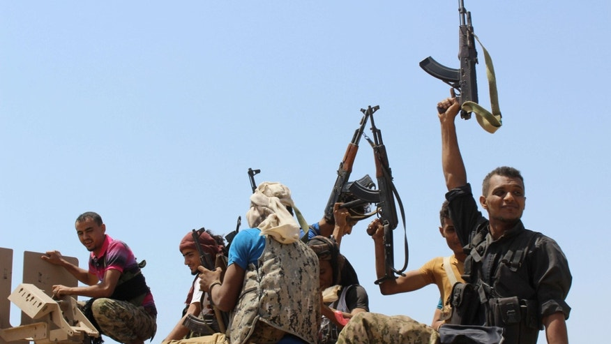 Oct. 2, 2015: Fighters against Shiite rebels known as Houthis hold up their weapons as they ride on an armored vehicle near the strait of Bab al-Mandab, west of the southern port city of Aden, to take back the control of the strait, Yemen.