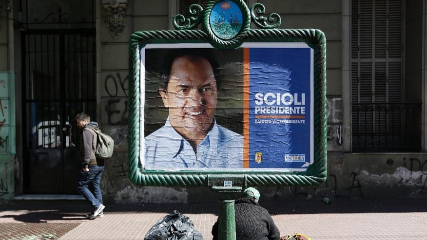 A homeless person sits in front of an campaign poster promoting presidential candidate Daniel Scioli, in Buenos Aires, Argentina, Friday, Oct. 23, 2015. President Cristina Fernandez hand-picked successor Scioli is leading in the polls for Sunday's presidential elections. (AP Photo/Jorge Saenz)